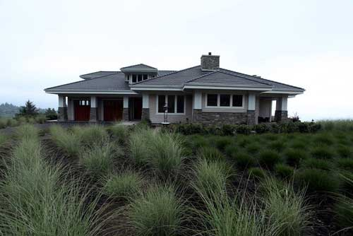 view of entire house in the front with bushes in the front