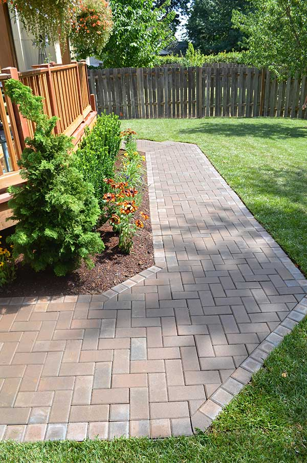 brick walkway around flower beds and rear house deck