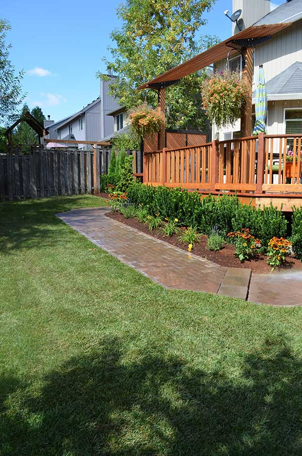 diagonal view of mulched plant beds with shrubs and flowers surrounding large wood deck 4