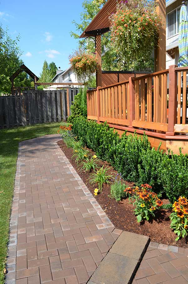 diagonal view of mulched plant beds with shrubs and flowers surrounding large wood deck 5