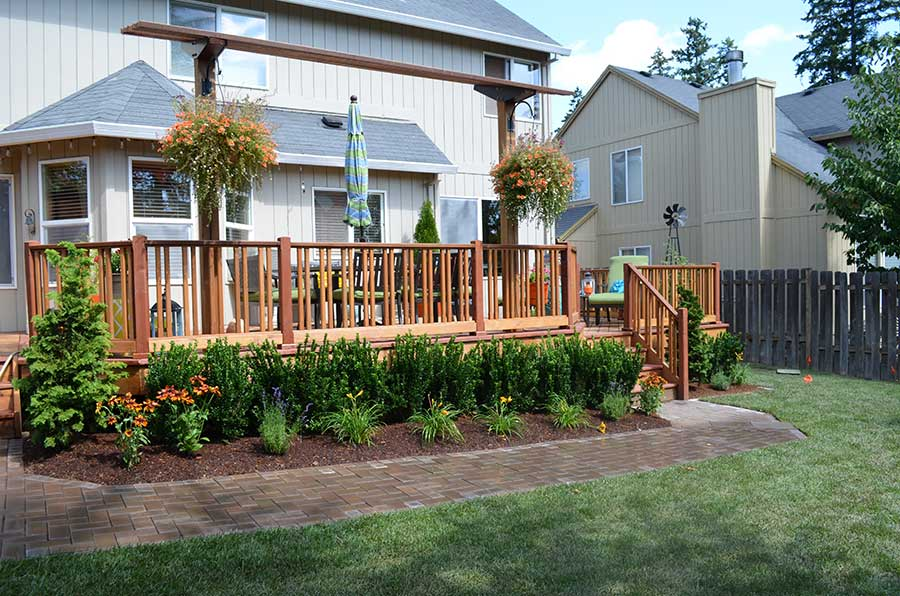 mulched plant beds with shrubs and flowers surrounding large wood deck 3