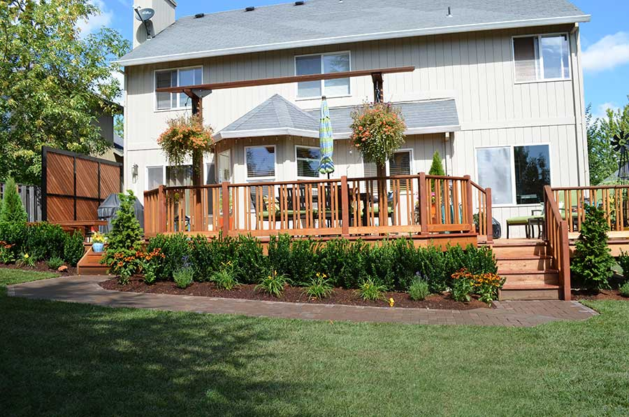 mulched plant beds with shrubs and flowers surrounding large wood deck