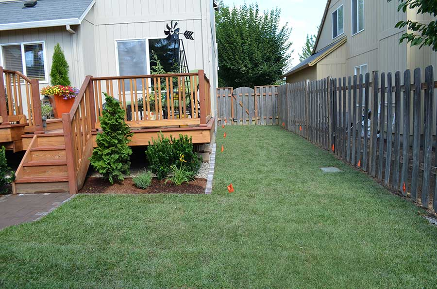 neat turf side yard ending with gated fence