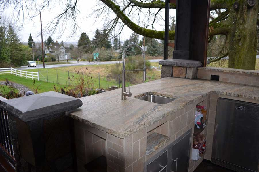 stone patio with countertop sink looking outwards to yard