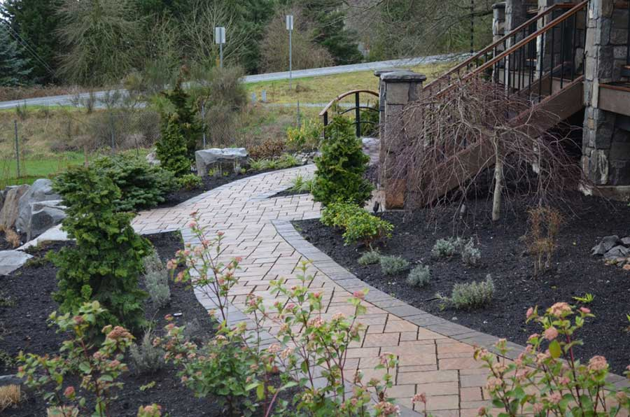 intricate brick pathway surrounding entryway with plantbeds of evergreen and succulents 2