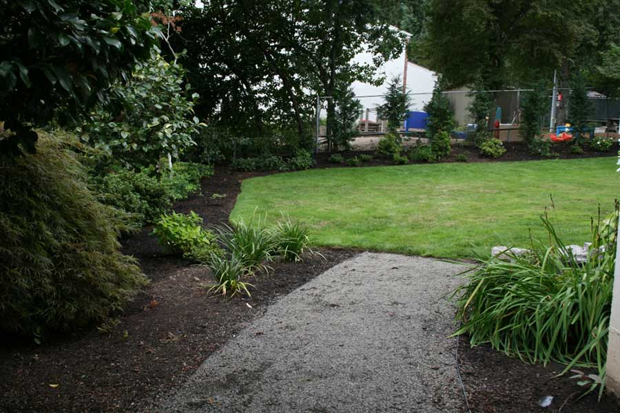 gravel path lined with plants and trees 3