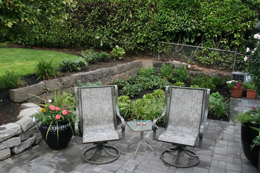 patio chairs and small table on stone patio with retaining wall 2