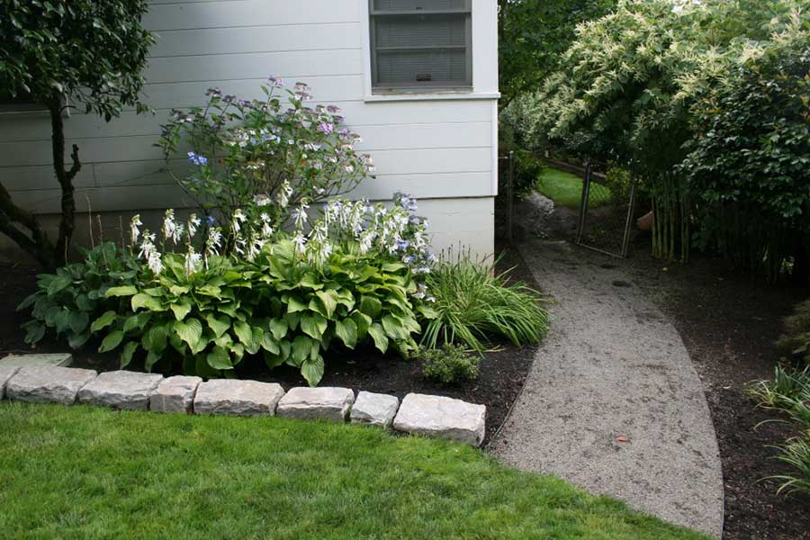 shaded gravel path and rock lined plant bed