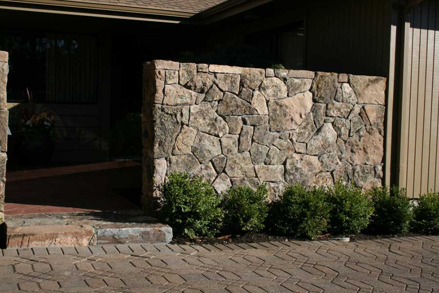 large natural stone wall and front door stoop