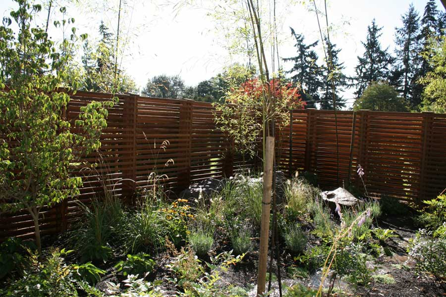wild plants garden with natural stone path and horizontal slat wooden fence 5