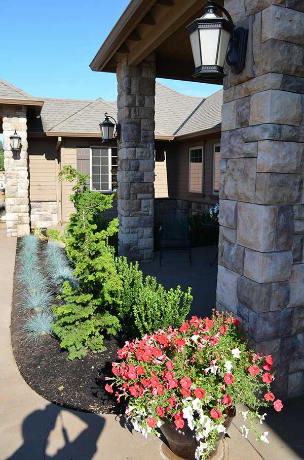 closeup of front entry stone columns and lining plant bed of low vegetation