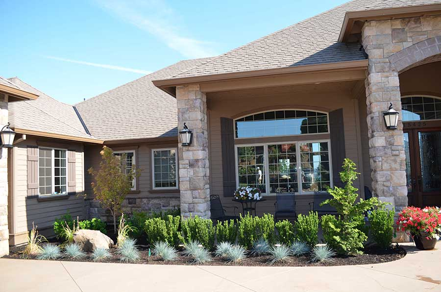 front entry stone columns and lining plant bed of low vegetation