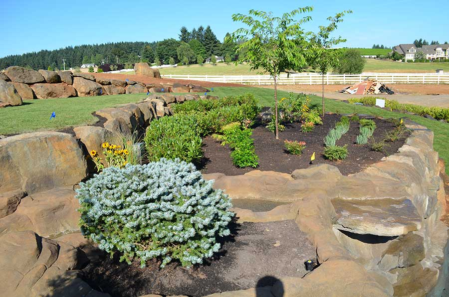 plant beds surrounded by water feature water flows