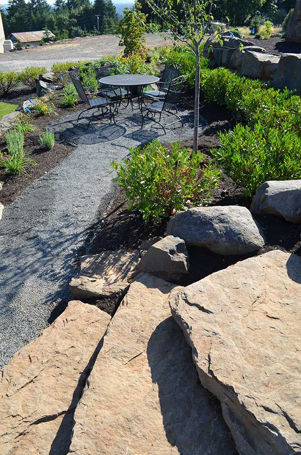 secluded plant lined gravel patio with furniture