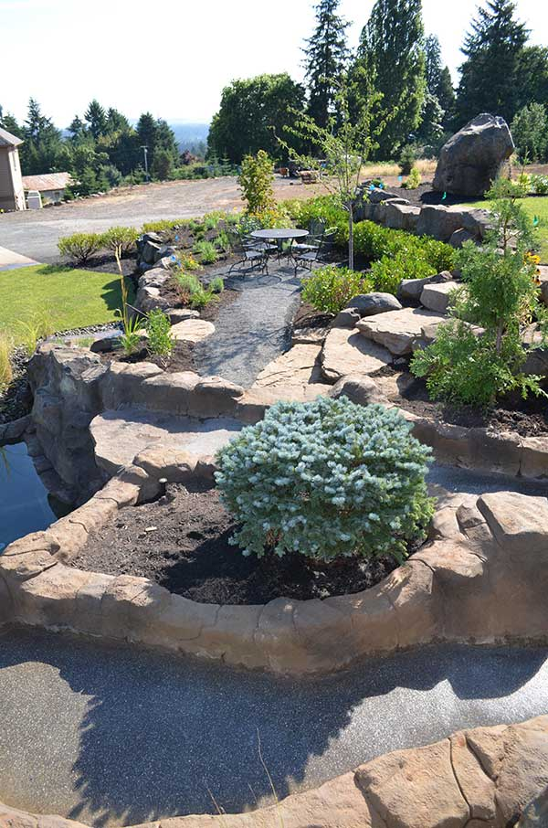 small plant bed surrounded by waterfall flows 2