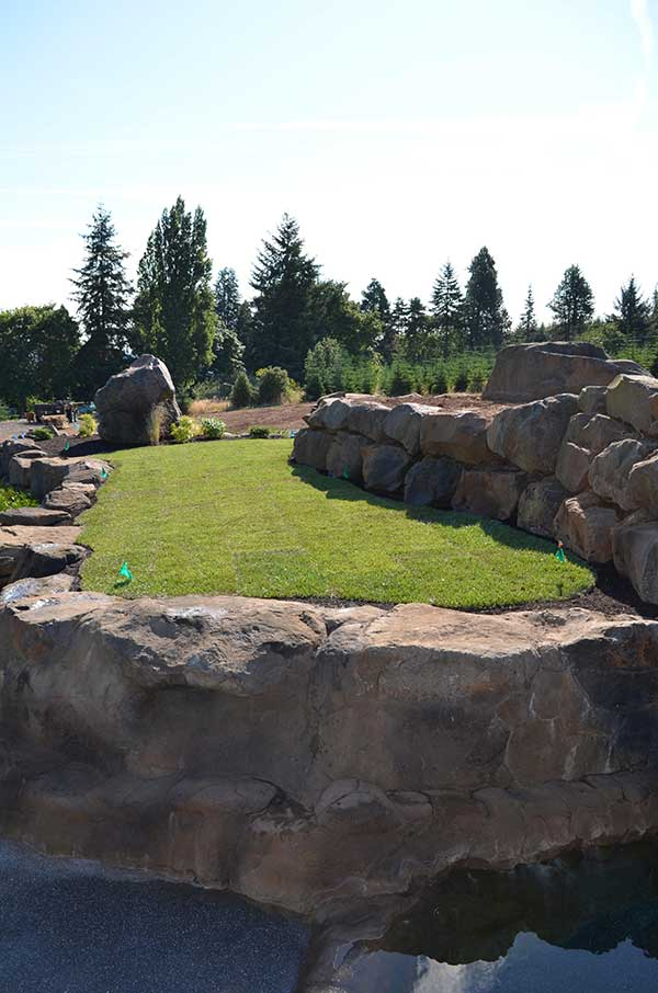 stone and concrete retaining wall for elevated turf lawn