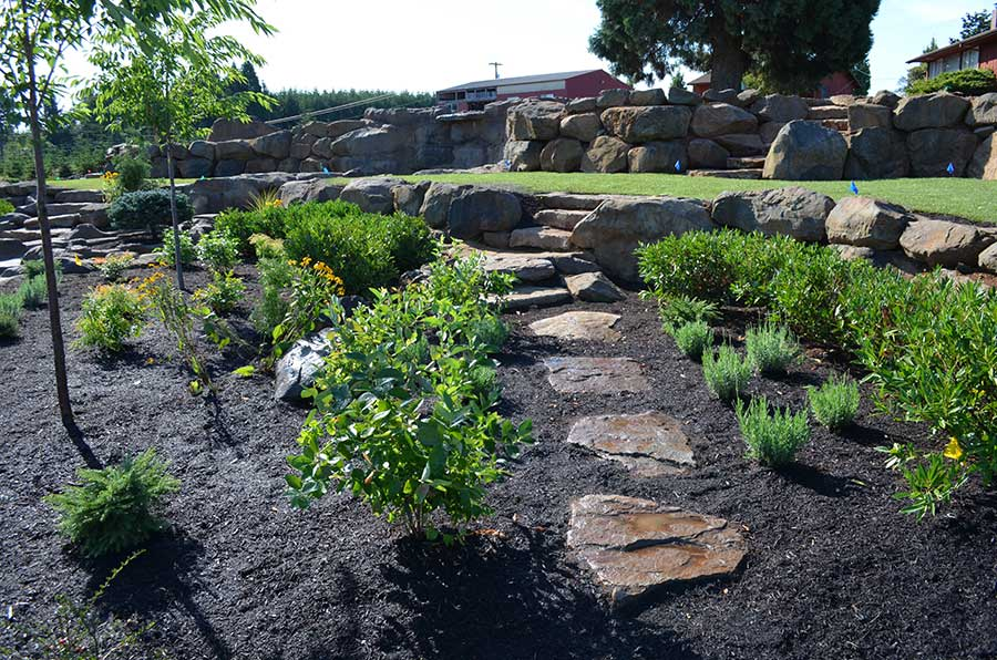 terraced yard with lower plant bed and large boulder retaining walls