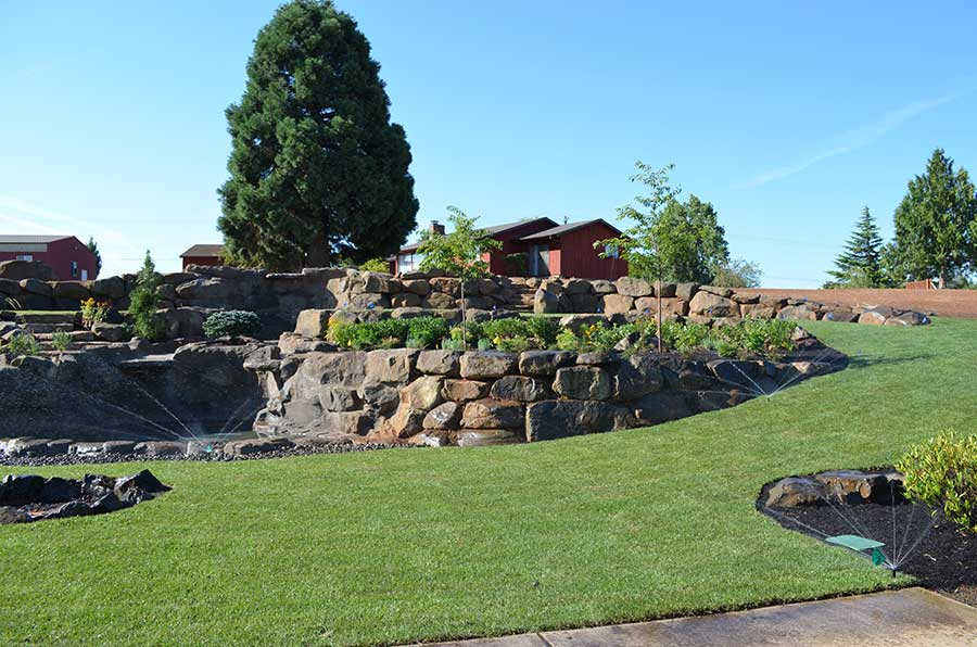 triple layer terraced lawn with curving retaining walls and sprinkler system