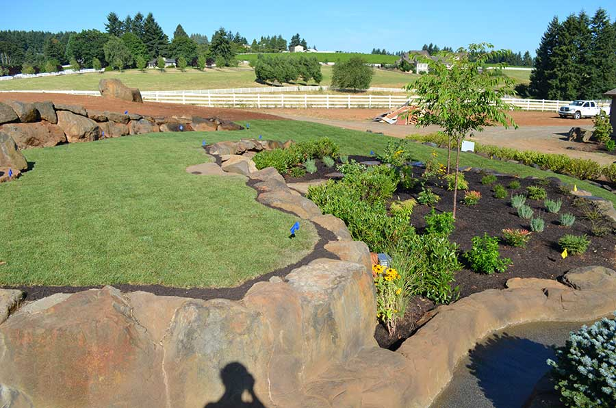 wide angle view from top of terraced garden looking towards driveway