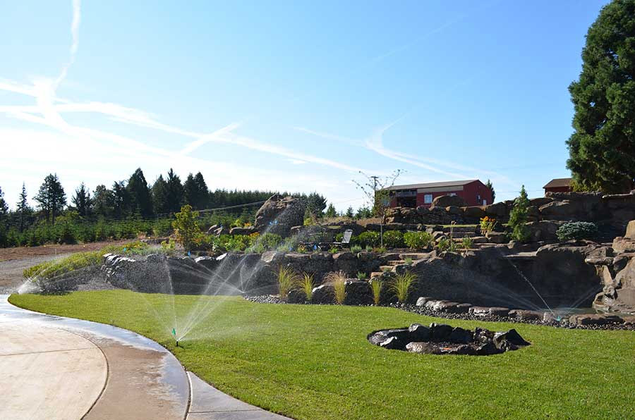 wide angle view of entire front landscaped yard being watered 2