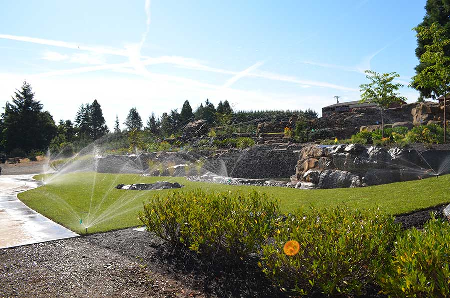 wide angle view of entire front landscaped yard being watered