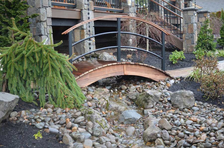 oriental style foot bridge over a small rocky brook 2