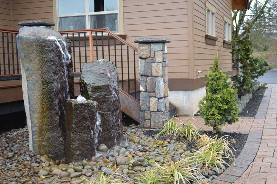 plant bed with rocks and cascading water feature over natural stone columns 2