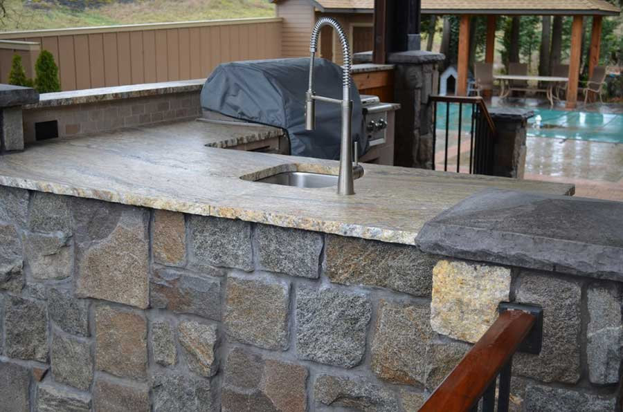 stone patio with countertop sink and barbeque