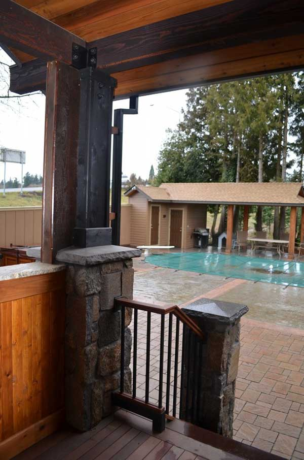 view from wood and stone balcony towards brick patio and covered pool