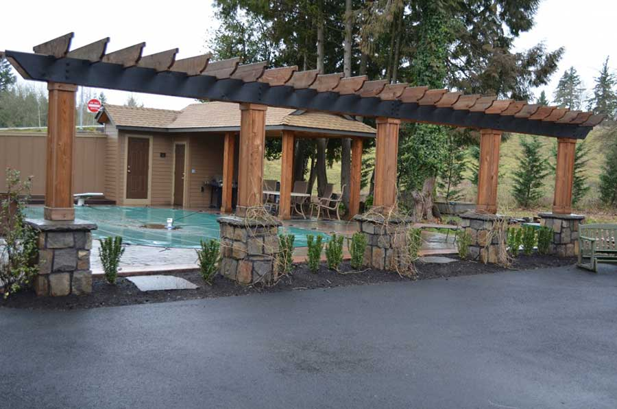 wood pergola planter and fence with flagstone supports in front of a covered pool and pool house