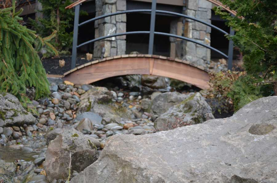 close ground view of oriental style foot bridge over a small rocky brook