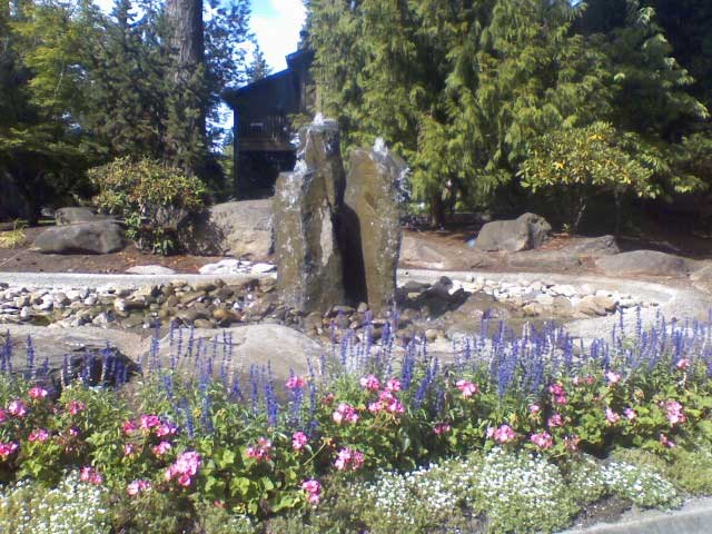natural stone columns water fountain surrounded by purple flowers 2