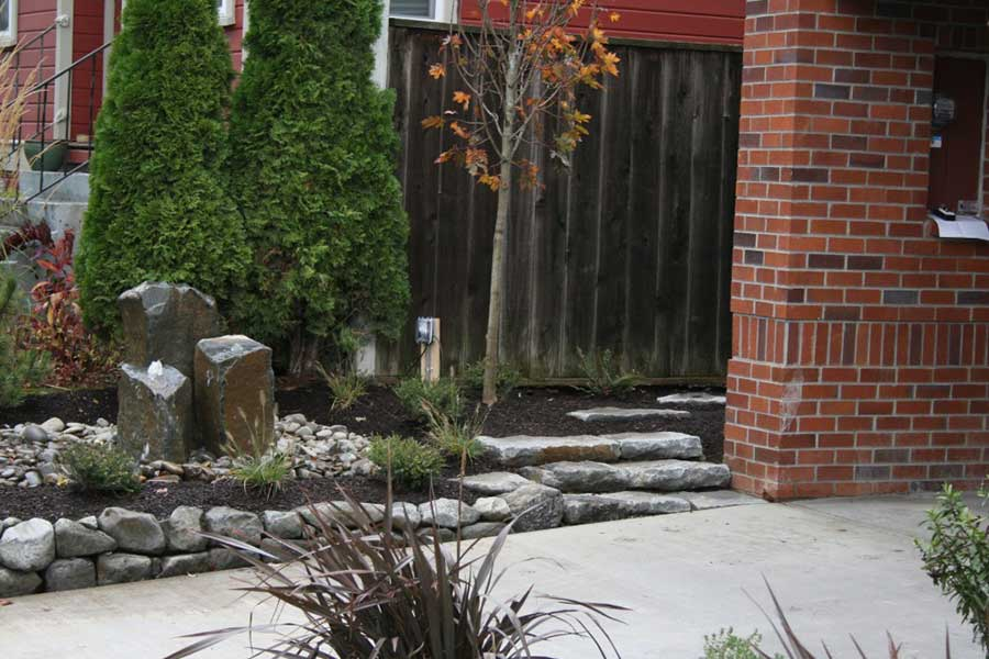 natural stone steps and retaining wall in front of square natural stone columns water feature
